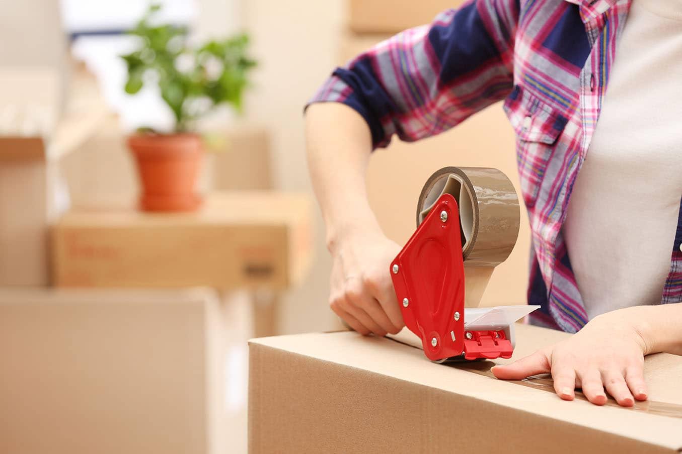 Woman using masking tape on moving box